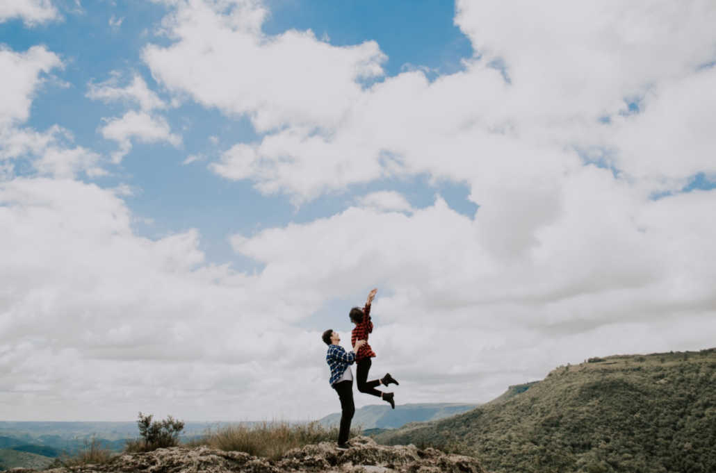 Man and woman smiling and jumping on mountain sexual health